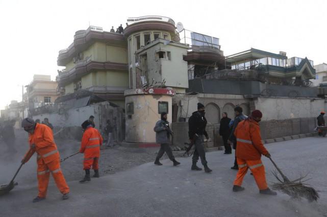 Des employés municipaux nettoient les rues au lendemain... (PHOTO RAHMAT GUL, AP)
