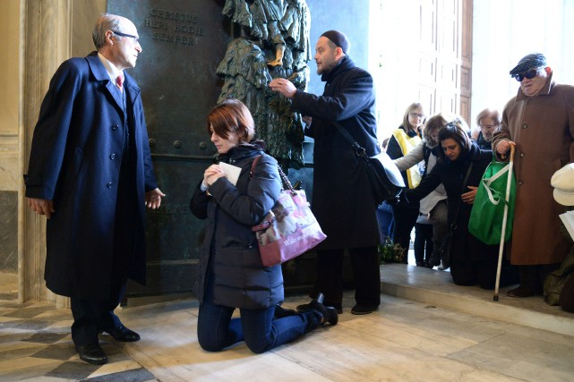 Des pèlerins franchissent l'une des «portes saintes» ouvertes... (PHOTO VINCENZO PINTO, AFP)