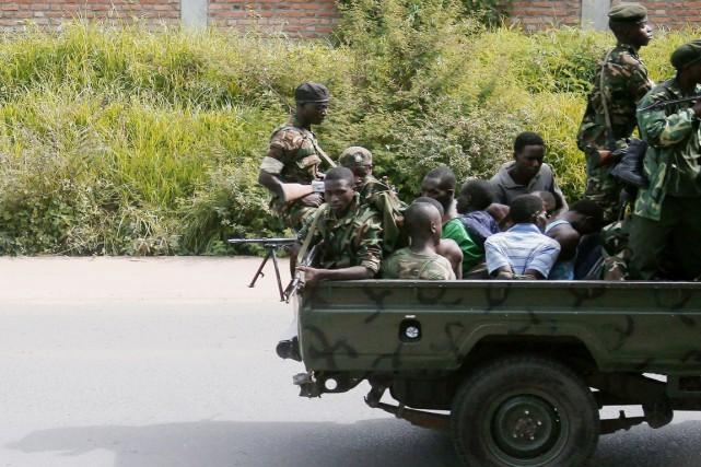 Des hommes attachés sont transportés dans un véhicule... (PHOTO ARCHIVES AFP/STRINGER)