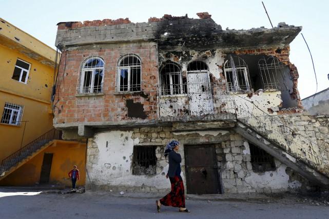 Une femme passe devant un bâtiment portant les... (PHOTO MURAD SEZER, ARCHIVES REUTERS)