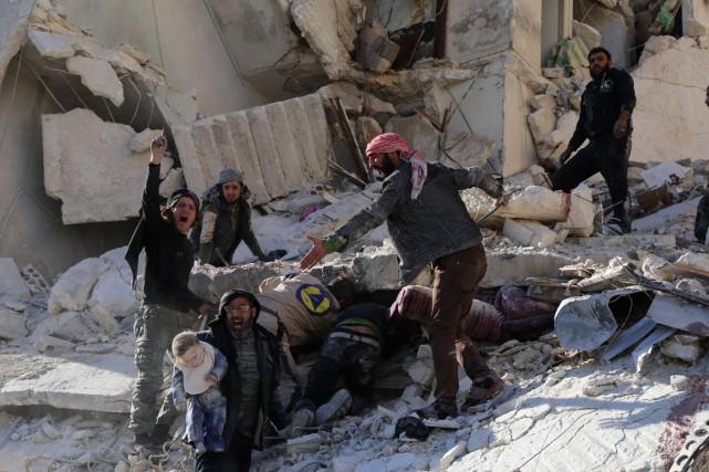 Des civils et des secouristes extraient des corps... (Photo BARAA AL-HALABI, archives AFP)