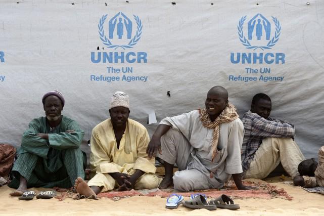 Des réfugiés Nigeriens attendent à l'extérieur d'une tente... (PHOTO PHILIPPE DESMAZES, AGENCE FRANCE-PRESSE)