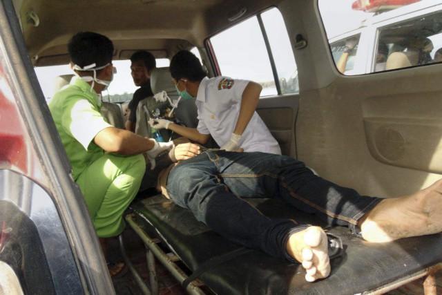 Des secouristes viennent en aide à un rescapé... (PHOTO IRWAN KAHIR, AFP)