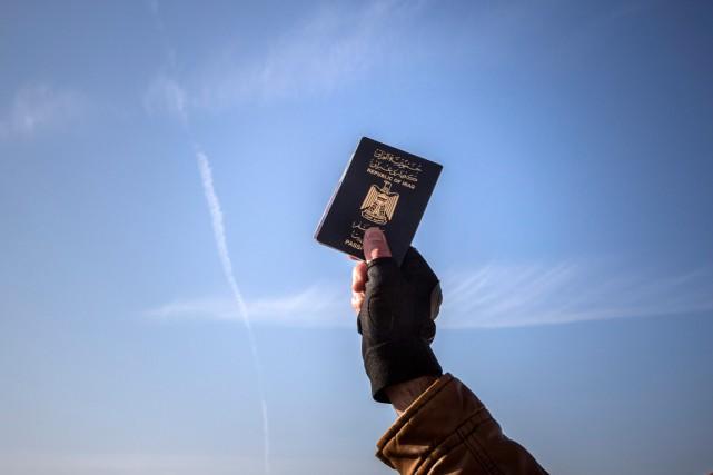 Un réfugié brandit son passeport irakien à son... (PHOTO SANTI PALACIOS, ARCHIVES AP)