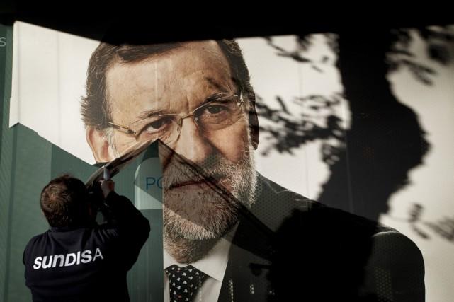 Un travailleur retire une affiche électorale à l'effigie... (PHOTO EMILIO MORENATTI, AP)