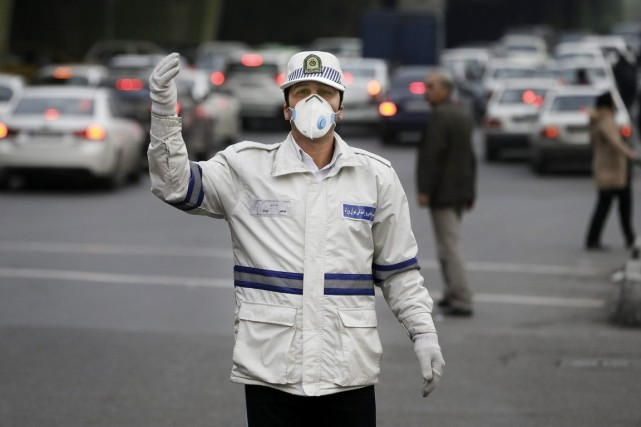 Un policier muni d'un masque antipollution régule la... (PHOTO VAHID SALEMI, AP)