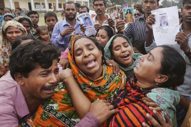 Des proches d'une victime de l'effondrement pleurent alors... (PHOTO KEVIN FRAYE, ARCHIVES AP)