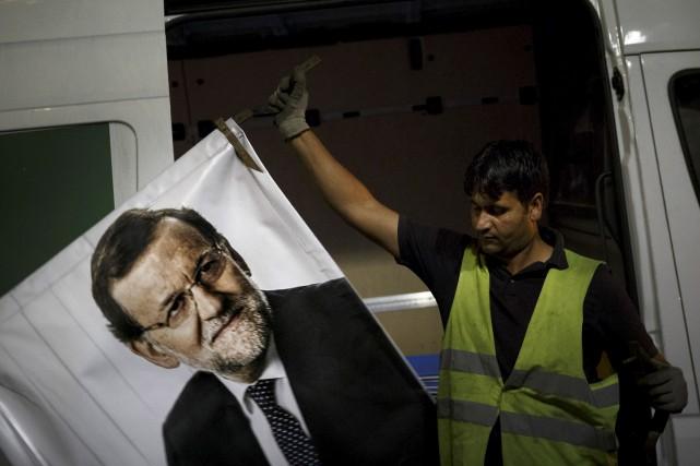 Un travailleur retire une affiche électorale à l'effigie... (AP, Daniel Ochoa de Olza)