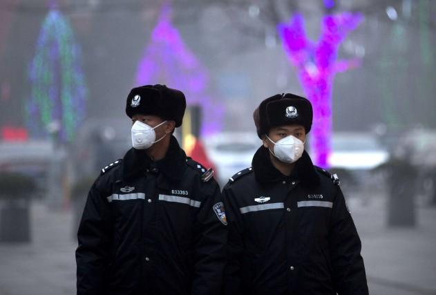 Des officiers de police couvrent leurs visages.... (Associated Press)