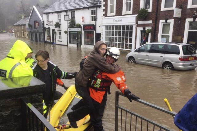 Un secouriste vient en aide à une dame... (PHOTO KIM PILLING, AP)
