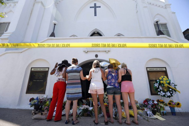 Un groupe de femmes prie devant l'église de... (PHOTO STEPHEN B. MORTON, AP)