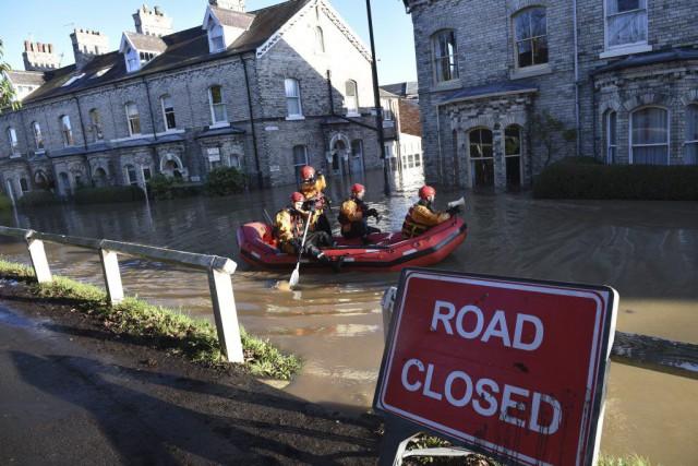Des secouristes cherchent des personnes ayant besoin d'aide... (PHOTO OLI SCARFF, AFP)