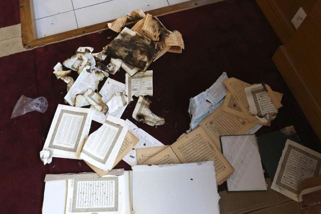 Des exemplaires du Coran ont été endommagés vendredi... (AP, Jean-Pierre Belzit)