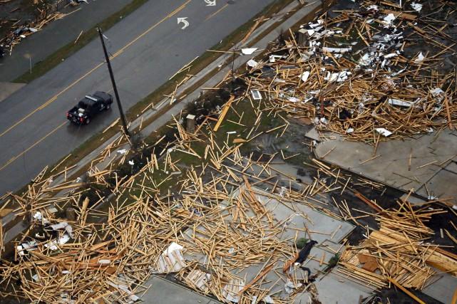 Une voiture roule au milieu des débris à... (Associated Press)