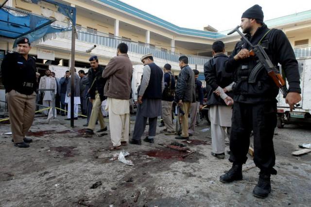 Des responsables examinentles alentours des bureaux de l'organisme... (Photo Mohammad Sajjad, AP)