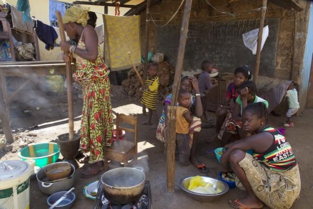 Des gens préparent de la nourriture à Conakry,... (AFP / Youssouf Bah)