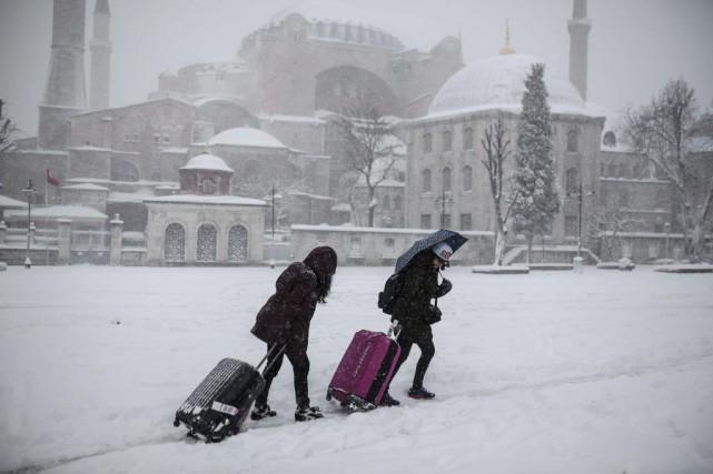 Des touristes tirent leurs valises dans la neige... (PHOTO YASIN AKGUL, AFP)
