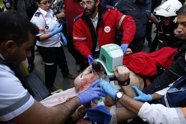 Des secouristes offrent les premiers soins à une... (PHOTO JACK GUEZ, AFP)