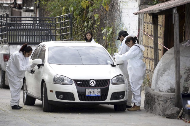 Des scientifiques analysent une voiture à l'extérieur de... (AP, Tony Rivera)