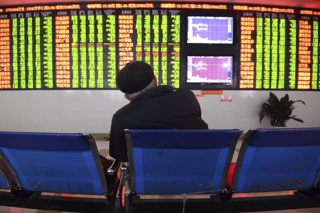 Un investisseur observe le comportement des cours boursiers... (AFP)