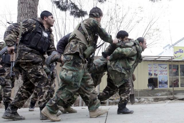Des membres des forces de sécurité afghanes transportent... (PHOTO ANIL USYAN, REUTERS)