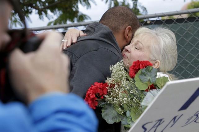 Les travailleurs s'enlacent avant le retour au travail... (Associated Press)
