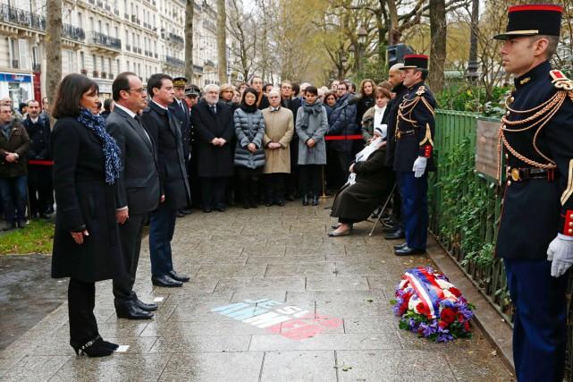 Entouré de la mairesse de Paris Anne Hidalgo... (PHOTO BENOIT TESSIER, AFP)