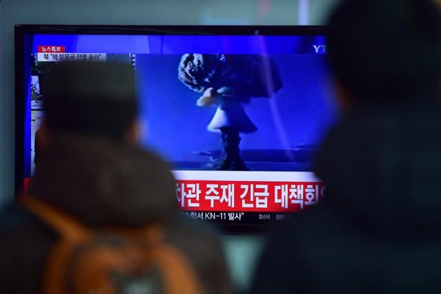 Des voyageurs regardent sur un poste de télévision... (PHOTO AFP)
