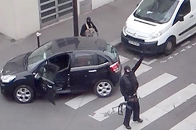 Les frères Kouachi retournent vers leur véhicule après... (IMAGE ARCHIVES REUTERS TV)