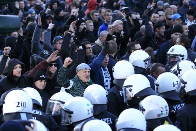 Des policiers sont aux aguets devant la foule... (PHOTO INA FASSBENDER, REUTERS)