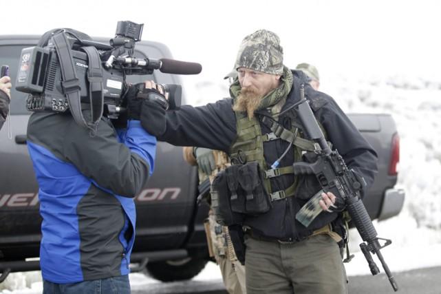 Un manifestant bloque l'objectif de la caméra d'un... (PHOTO AP)