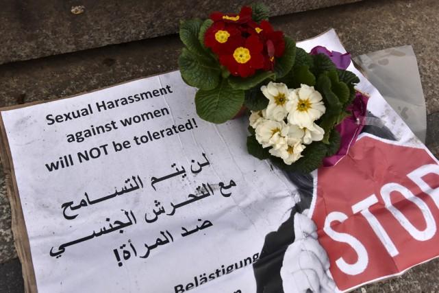 Une bannière avec des fleurs déposée en face... (Associated Press)