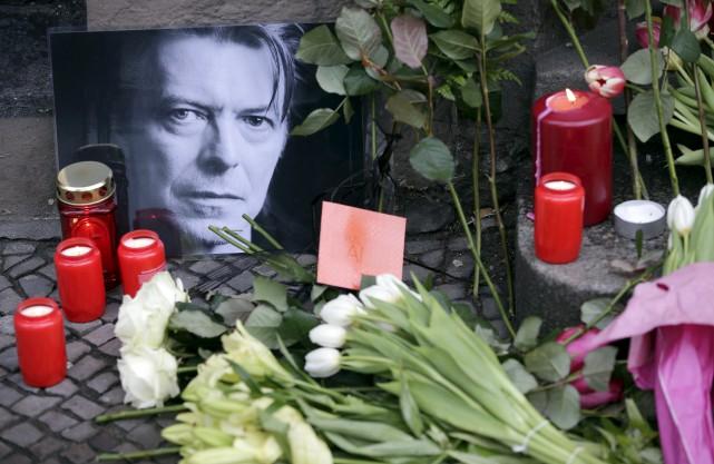 Fleurs, portraits, lampes et hommages ont été déposés... (Photo The Associated Press, Michael Sohn)