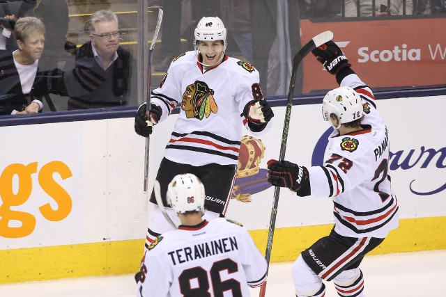 Patrick Kane (au centre) a réussi un tour... (Photo Tom Szczerbowski, USA TODAY)