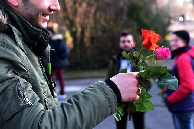 Un réugié marocain présente une fleur pendant qu'une... (PHOTO PATRIK STOLLARZ, AGENCE FRANCE-PRESSE)