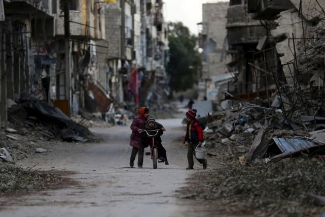 Des enfants jouent dans une rue, en banlieue... (Photo Bassam Khabieh, Reuters)
