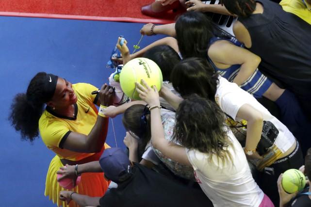 Serena Williams signe des autographes après avoir défait... (AP,  Aaron Favila)