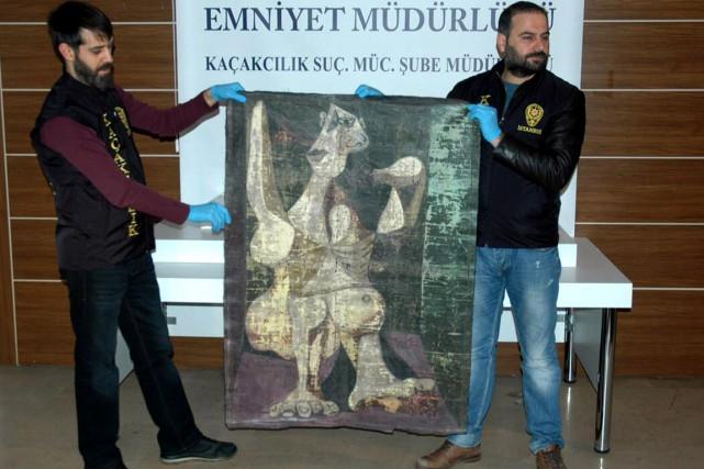 Des policiers turcs montrent la toile retrouvée lors... (Photo AFP)