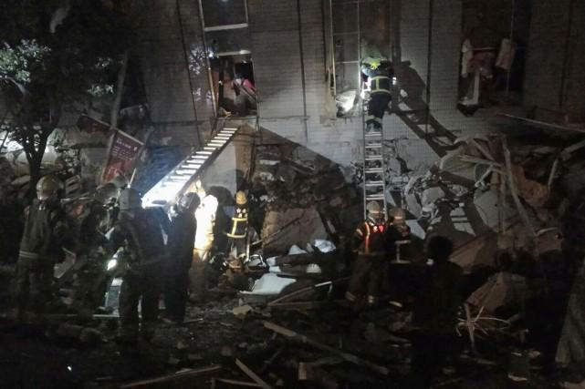 Des secouristes entrent à l'intérieur d'un bâtiment qui... (AP)