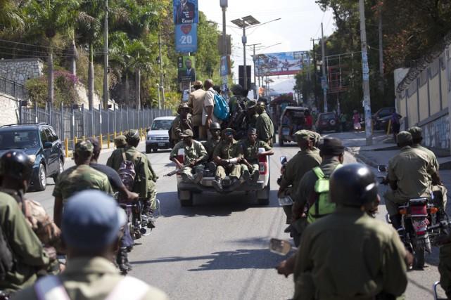 D'anciens membres de l'armée dissoute patrouillent, armés, dans... (Photo Dieu Nalio Chery, AP)
