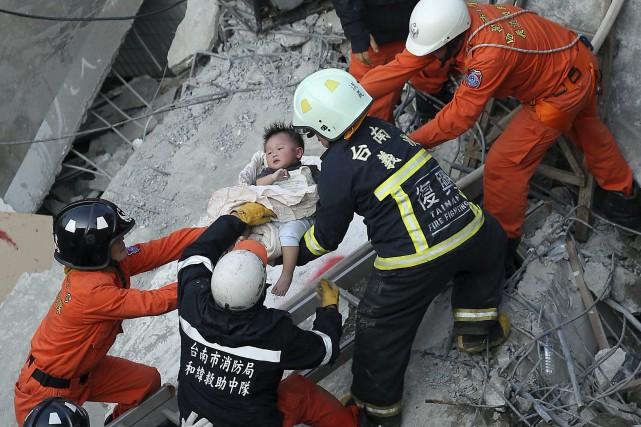 Un jeune enfant est secouru après que l'édifice... (PHOTO REUTERS)