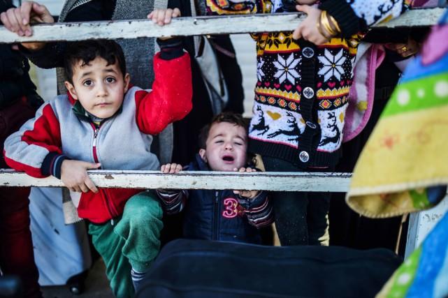 Devant la barrière toujours abaissée du poste-frontière turc... (PHOTO BULENT KILIC, AFP)