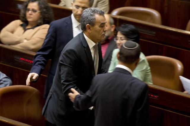 Jamal Zahalka est escorté à l'extérieur dela Knesset,lundi.... (PHOTO AP)