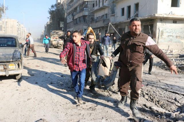 Des hommes transportent le corps d'une victime, tuée... (PHOTO AMEER AL-HALBI ARCHIVES AFP)