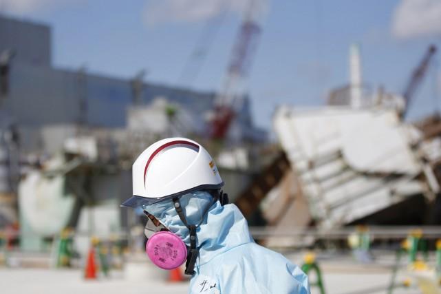 Un travailleur de TEPCO muni d'une combinaison et... (PHOTO TORU HANAI, AP)
