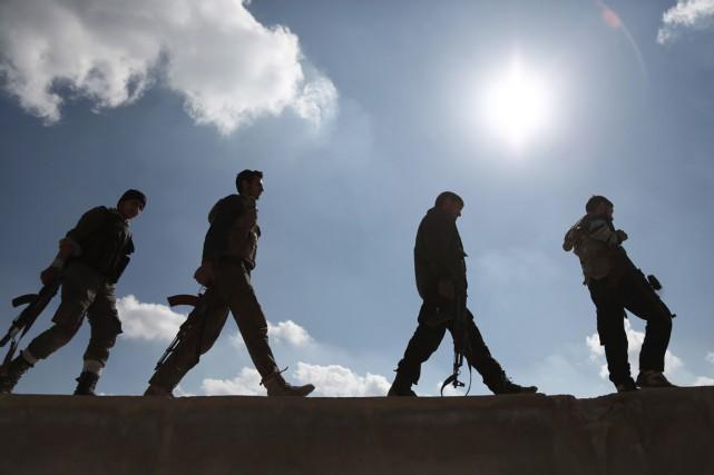 Des combattants rebelles marchent dans Ghouta, bastion de... (PHOTO AMER ALMOHIBANY, ARCHIVES AFP)
