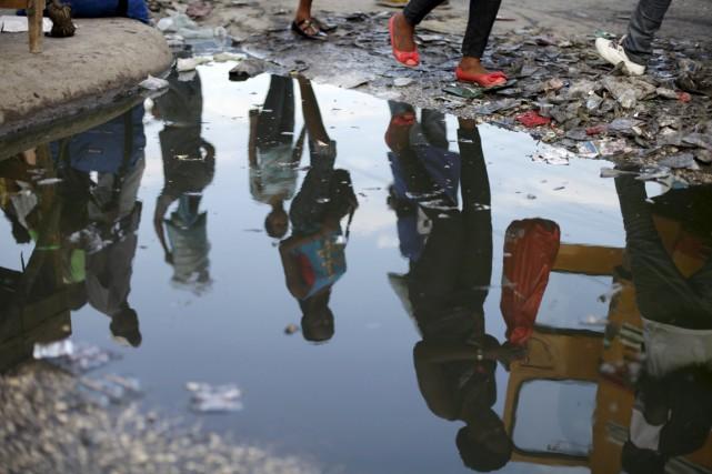 L'image de résidants de Port-au-Prince se reflète dans... (PHOTO ANDRES MARTINEZ CASARES, REUTERS)
