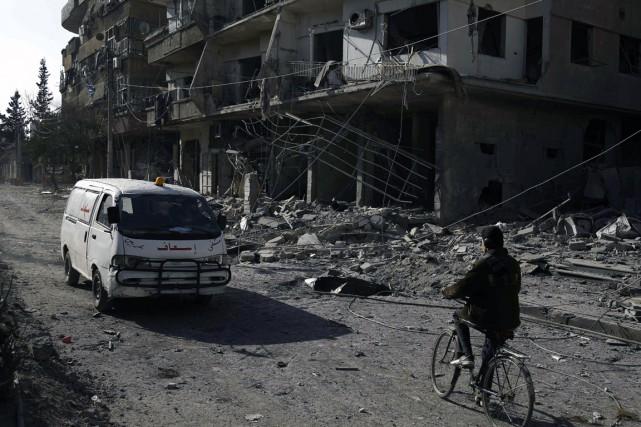 Une ambulance dépasse des immeubles endommagés par des... (Photo ABDULMONAM EASSA, AFP)