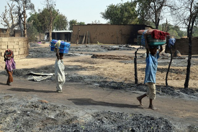 Des enfants fuyant Boko Haram transportent leurs biens,... (Photo archives AFP)