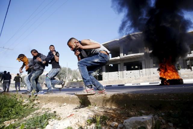 De jeunes protestataires palestiniens tentent de se mettre... (PHOTO MOHAMAD TOROKMAN, REUTERS)